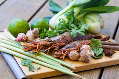 Ingredients for Thai tom yam soup. Laid out on a kitchen counter with tiger prawns, mushrooms, ginger, lemongrass, limes, celery, parsley and spices Royalty Free Stock Photos
