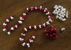 Ingredients to Make a Christmas Garland. Fresh cranberries and popcorn on a wooden tabletop with a partially made Christmas garland on thread with the next piece royalty free stock photo
