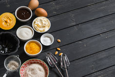 Ingredients to prepare pumpkin cake with chocolate - flour, sugar, pumpkin puree, butter, pumpkin, chocolate, baking dish Royalty Free Stock Photo