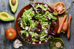 Ingredients to prepare a salad. High-angle shot of a rustic wooden table with some ingredients to prepare a salad; a plate with lettuce mix, tomatoes, an avocado Royalty Free Stock Image