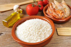 Ingredients to prepare a spanish paella or arroz negro. Some ingredients to prepare a spanish paella or arroz negro, such as rice, tomato, garlic or shrimps, on royalty free stock photos