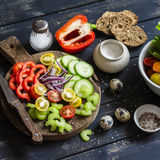 Ingredients to prepare vegetable salad - tomatoes, cucumber, celery, bell pepper, red onion, quail eggs, garden herbs and spices o Stock Photo