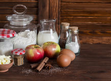 Ingredients and tools for baking - flour, eggs, butter, apples, cinnamon on a brown rustic wooden surface. Stock Image