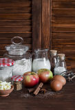 Ingredients and tools for baking - flour, eggs, butter, apples, cinnamon on a brown rustic wooden surface. Royalty Free Stock Images