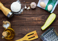 The ingredients and tools for cooking pancakes from zucchini  on a dark wooden background. Stock Photography