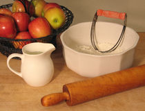 Ingredients and tools for making a pie. Basket of apples, flour in a bowl, ice water in a pitcher, along with rolling pin and pastry cutter Royalty Free Stock Photo