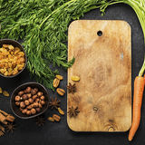 Ingredients for the traditional classic carrot flavored autumn seasonal pie: juicy fresh carrots, raisins, spices. Spices, honey, nuts on a dark background Royalty Free Stock Photos