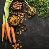Ingredients for the traditional classic carrot flavored autumn seasonal pie: juicy fresh carrots, raisins, spices. Spices, honey, nuts on a dark background Royalty Free Stock Image