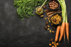 Ingredients for the traditional classic carrot flavored autumn seasonal pie: juicy fresh carrots, raisins, spices. Spices, honey, nuts on a dark background Royalty Free Stock Images