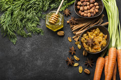 Ingredients for the traditional classic carrot flavored autumn seasonal pie: juicy fresh carrots, raisins, spices. Spices, honey, nuts on a dark background Royalty Free Stock Photo
