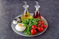 Ingredients for the traditional Italian caprese salad on a glass tray on a grey background with bottles of olive oil and Royalty Free Stock Photo