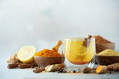 Ingredients for turmeric hot tea on grey background. Healthy ayurvedic drink with lemon, ginger, cinnamon, turmeric. Immune royalty free stock images