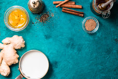 Ingredients for turmeric latte on cyan background top view. Milk, ginger , cinnamon , pepper , turmeric paste and honey on the cyan background top view royalty free stock photos