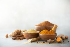 Ingredients for turmeric latte. Ground turmeric, curcuma root, cinnamon, ginger, black pepper on grey background. Spices stock photo