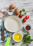 Ingredients and utensils for cooking fried eggs with tomatoes: eggs, tomatoes, spices, herbs and  pan Royalty Free Stock Images