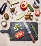 Ingredients for vegetarian salad, cucumbers, eggplant, red bell pepper, tomatoes, spices herbs, lies next to a cutting board a Stock Photography