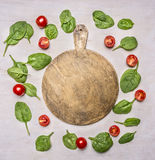 Ingredients for vegetarian salad with spinach and cherry tomatoes, laid out around round cutting board on wooden rustic backgrou royalty free stock images