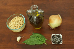 Ingredients for White Bean Dip. Ingredients for recipe for White Bean Dip on a dark wood table top - cannellini beans, olive oil. onion, garlic clove, basil royalty free stock image