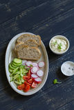 Ingredients for whole wheat toasts with cheese, radish, cucumber, cherry tomatoes Royalty Free Stock Images