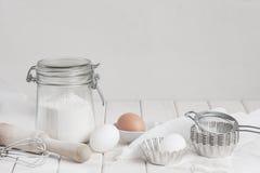 Ingredietns für Kuchen auf der weißen Tabelle Stockfotos