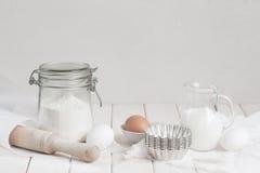 Ingredietns para las tortas en la tabla blanca foto de archivo