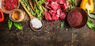 Ingrediënten voor goelasj of hutspot die koken: ruwe vlees, kruiden, kruiden, groenten en lepel van zout op rustieke houten achte Royalty-vrije Stock Fotografie