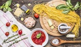 Ingrediënten voor het koken van deegwaren, tomaten in eigen sap, basilicum, garnalen, rasp, kersentomaten, houten lepel, hakbordh Royalty-vrije Stock Foto