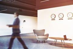 Ingresso bianco dell'ufficio con gli orologi e le poltrone, uomo Fotografia Stock