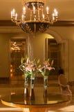 Ingresso dell'hotel con il lampadario a bracci ed i fiori Immagini Stock Libere da Diritti