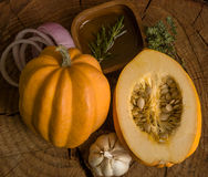 Ingridients for baked pumkin. Fresh vegetables and herbs on a wooden background Royalty Free Stock Photos