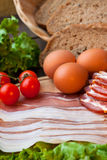 Ingridients for breakfast. Eggs and bacon - vertical stock image