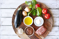 Ingridients for cooking Parmigiana di melanzane. Baked eggplant - italy, sicily cousine. On the wooden table royalty free stock photo