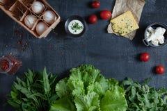 Ingridients para cocinar la ensalada Verduras, huevos del eco y verdes frescos, orgánicos tomate y quesos en fondo de piedra oscu fotos de archivo