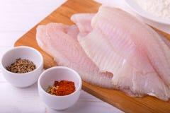 Ingridients para o tilapia fritado dos peixes Faixa crua, fleur, cominhos fotografia de stock