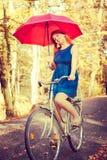 Ingwerhaarmädchen hält roten Regenschirm Lizenzfreies Stockbild