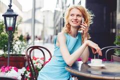 Ingwermädchen im blauen Kleid sprechend am Telefon, Foto getont stockbilder