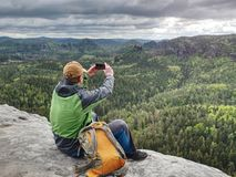 Ingwermann macht Fotos mit intelligentem Telefon auf felsiger Spitze lizenzfreie stockfotografie
