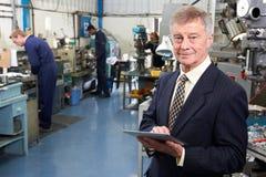 Inhaber der Technik-Fabrik mit Personal im Hintergrund Lizenzfreies Stockfoto