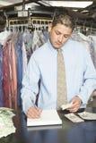 Inhaber mit den Empfängen und den Banknoten Konten am Zähler analysierend Lizenzfreie Stockfotos
