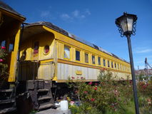 Inhabitated  train coach parked in red roses Royalty Free Stock Images