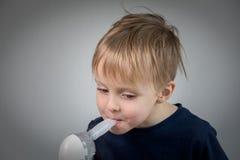 Inhalación takeing del niño pequeño para el didease respiratorio Foto de archivo libre de regalías