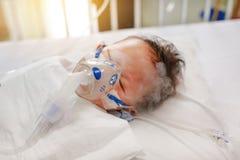 Inhalacyjny chłopiec wiek o 1 lat na cierpliwym łóżku Oddechowy syncytial wirus RSV Intensywna opieka na łóżku przy szpitalem obraz royalty free