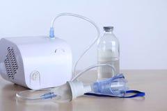 Inhalator mask vapor on a white background. Close-up inhalator mask vapor on white background. Steam nebulizer and medicine on the table Royalty Free Stock Photo