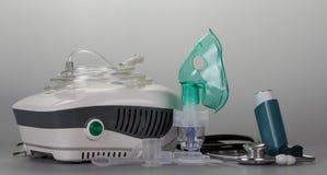 Inhaler συμπιεστών με τη μάσκα, μικρή συσκευή τσεπών για το asthmatics και phonendoscope σε γκρίζο Στοκ φωτογραφία με δικαίωμα ελεύθερης χρήσης