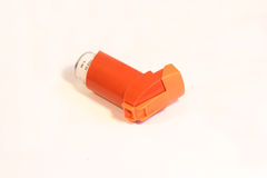 Inhaler. Orange asthma inhaler on a white background Stock Photos