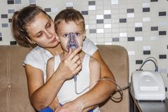 Inhaler for cough. Mom makes his son inhalation for bronchitis from coughing. Breathe in inhaler mask. Royalty Free Stock Photography