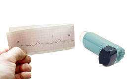 Inhaler to treat asthma and cardiogram in hand Royalty Free Stock Photo