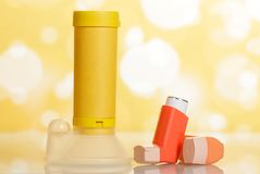 Inhalers and aerochamber on abstract yellow. Inhalers and orange aerochamber on abstract bright beautiful yellow background Royalty Free Stock Photos