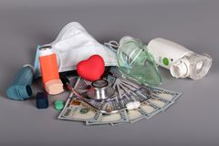 Inhalers and mask, stethoscope, money for diagnostics and treatment, on gray. Background stock photo