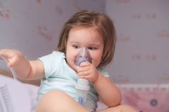 Inhaling. Little baby girl holding inhaler stock photo